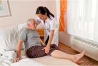 A caregiver assists her patient to lie in bed