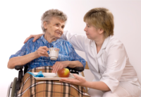 A caregiver assists her patient in having a meal