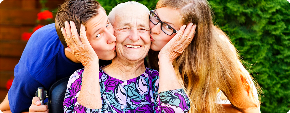 Grand children kiss their grand mother