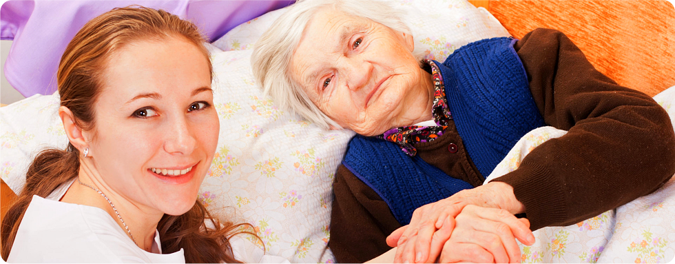 A caregiver holds the hands of her patient