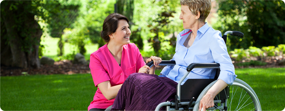 A patient on a wheelchair with her caregiver